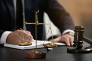 Lawyer sitting at a desk with a gavel and scales in the foreground.